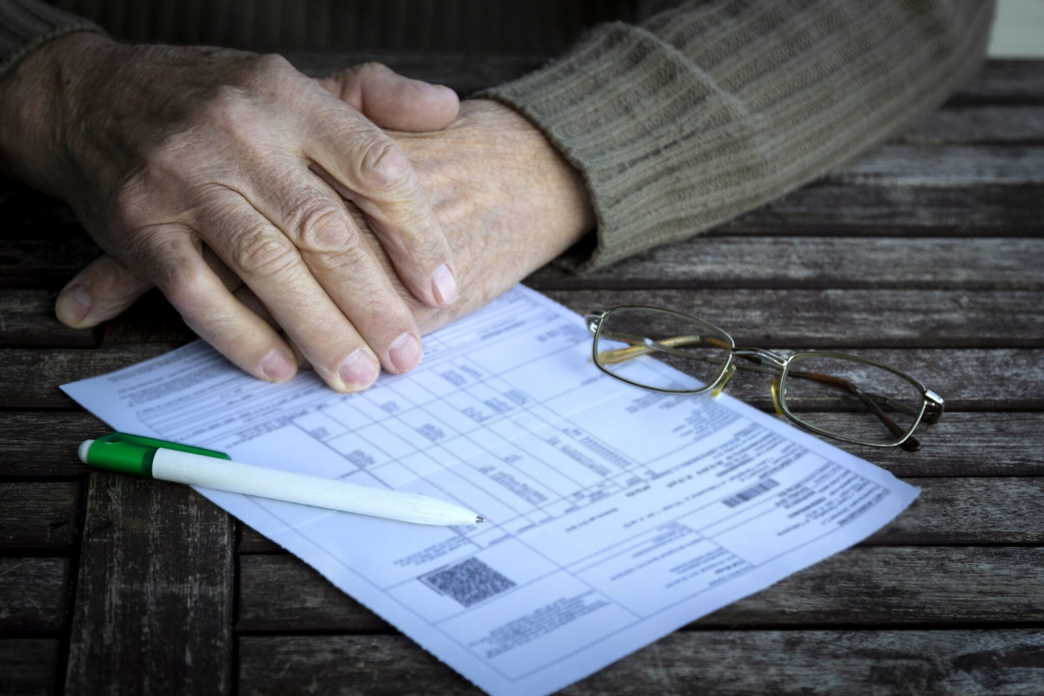 Hands of senior next to a form