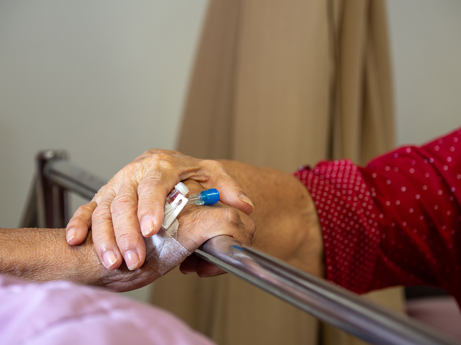 Woman holding hand of person in hospital