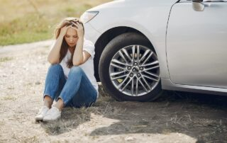 A woman is sitting beside her car after dealing with an auto accident