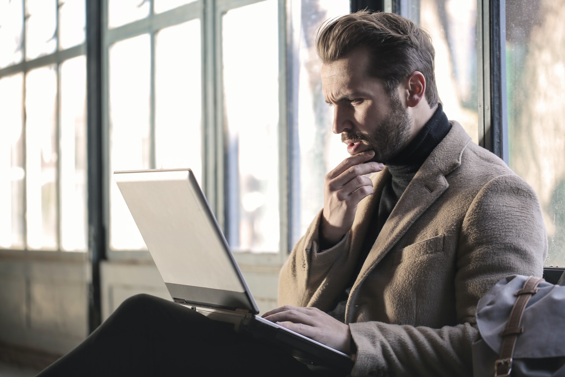 Man sitting with laptop and a confused look on his face