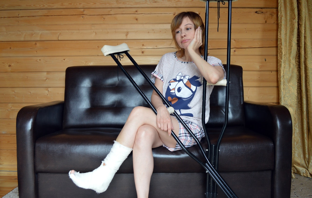 Sad young woman sitting on the couch with a broken leg in a cast, and her crutches
