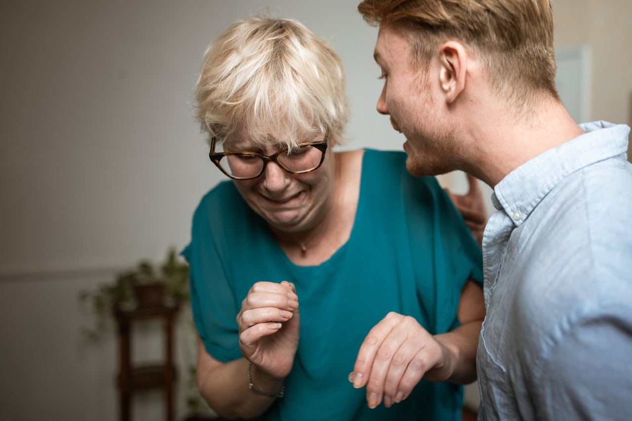 Young adult man yelling at an elderly woman